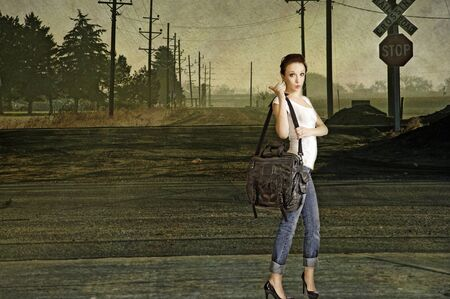 hitch hiker: Sexy young redhead hitchhiking on a lonely country road. Composite Stock Photo