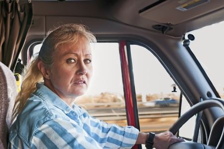 trucker: Pretty adult woman driving a big truck down the highway. Stock Photo