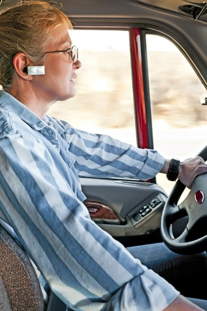 Pretty adult woman truck driver talking on her hands-free bluetooth device connected to her cellphone.