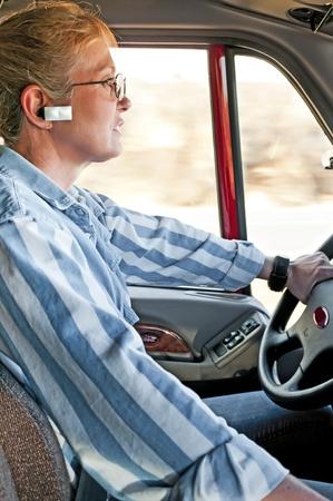 Piuttosto adulto camionista donna che comunica sul suo dispositivo vivavoce bluetooth collegato al suo cellulare. Archivio Fotografico - 11291826