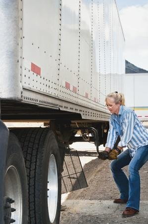 dolly: Bella bionda camionista donna gira la manovella dolly a sollevare le gambe di una traier dopo aver eseguito il suo trattore sotto di essa. Archivio Fotografico