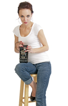 folding camera: Attractive young woman with a vintage folding camera and a remote shutter release. Stock Photo
