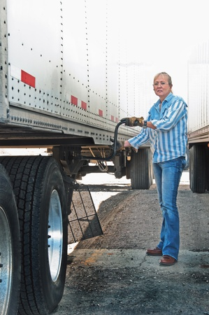Blonde woman truck driver cranking the dolly stand up on a semi-trailer, getting ready to haul a load of merchandise across country.