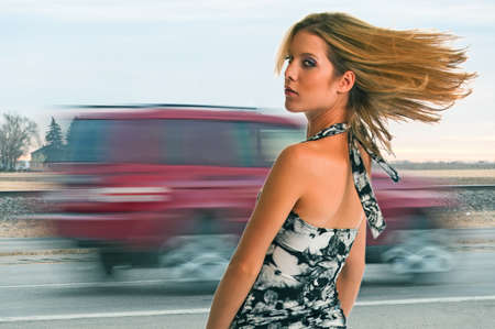 Pretty blonde girl standing near fast moving cars with her hair flowing with the traffic. Firm footing in a fast moving world. Girl is grounded and strong.