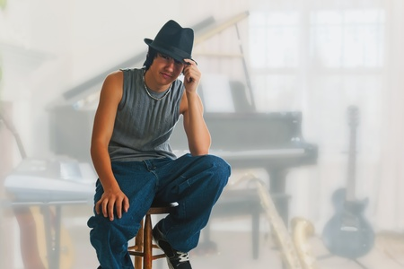 Young blues player resting during a jam session break, sitting on a stool wearing a black fedora. photo