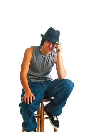 Handsome young man sitting cool in a fedora on a stool. Isolated on a white background.
