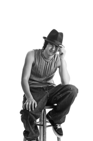 Handsome young man sitting cool in a fedora on a stool. Isolated on a white background. Black and White. photo