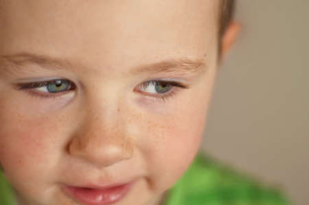 Cute little boy with camera focus on his beautiful clear blue eyes Banco de Imagens