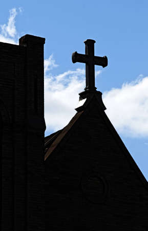 Iron cross on top of a Christian church steeple silhoueted against a blue sky Stock Photo - 12751352