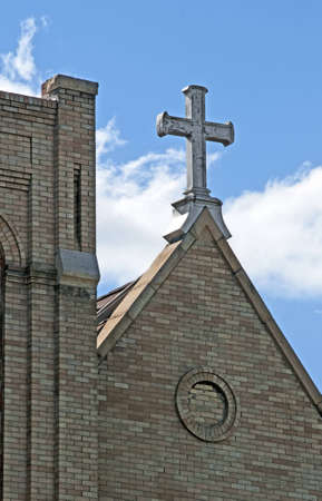 Iron cross on top of a Christian church steeple against a blue sky  Stock Photo - 12751354