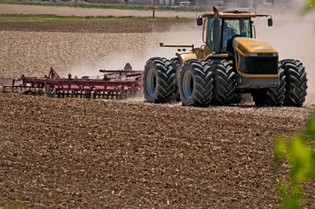 Farmer stirring up dust using a disc harrow to prepare his field for planting