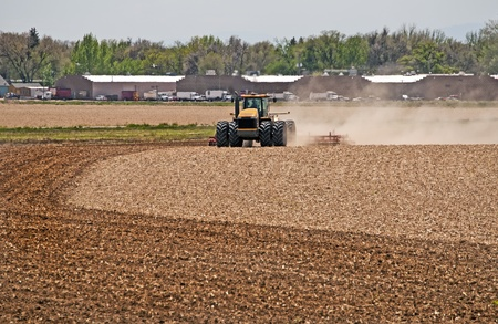 Farmer in a large tractor pulling a disc harrow through his field to break up the soil for spring planting