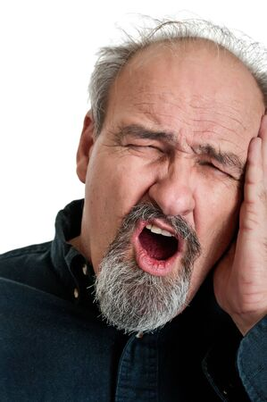 Balding man in his sixties holding his head in pain as he shouts. Isolated on a white background. Stock Photo - 12751584