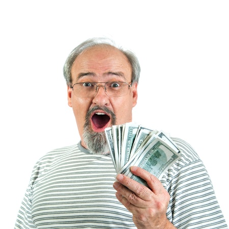 man holding money: Adult male showing a look of amazement and surprise while holding a handful of one hundred dollar bills of American money.