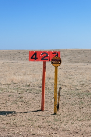 Oil pipeline marker and sign on the Pawnee National Grasslands in northern Colorado, USA. The numbers on the orange sign are easily read from a low flying plane if problems are spotted during a flyover.
