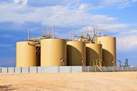 yacimiento petrolero: Crudo Tanques de almacenamiento de petr�leo en el centro de Colorado, EE.UU. Foto de archivo