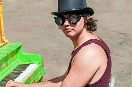 steampunk goggles: Youn hombre en un sombrero de copa y gafas tocando un piano de colores al aire libre.