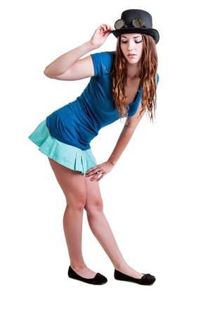 falda corta: Chica joven bonita en una falda corta con un sombrero de vapor-punk con gafas. Aislado contra un fondo blanco