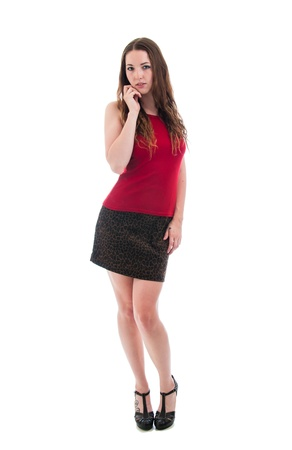 body curve: Pretty brunette girl in a short skirt with red camisole and heels isolated against a white background.
