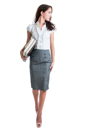 Pretty young businesswoman or student looking over her shoulder while carrying books. Isolated against a white background photo