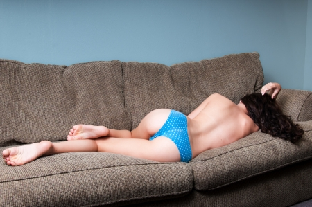 Sexy young woman sleeping on her couch at home in just her blue panties.