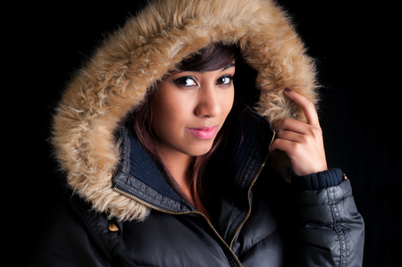 parka: Beautiful young woman wearing a parka with imitastion fur lining. Stock Photo