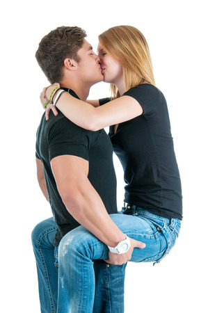 Strong young man holding his lover while kissing her. photo