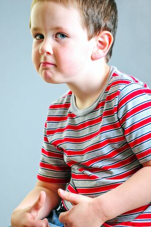 tough guy: Cute little boy putting on his best tough guy look against a grey background.