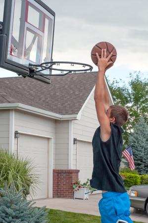 Teenage boy practicing basketball at home on his driveway in a suburban neighborhood photo