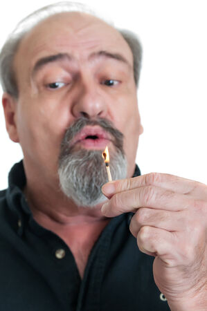 blow out: Mature male ready to blow out a burning match before it gets to his fingers. Stock Photo