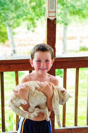 Cute little boy with no shirt in the summer carrying a cat in his arms.