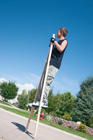 stilts: Teenage boy learning to walk on stilts he just finished making.