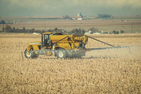 Farmer spraying fertilizer onto his field before plowing