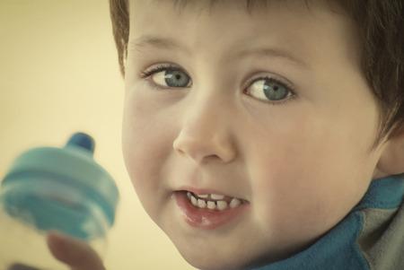 nursing bottle: Cute little baby boy holding a bottle. Retro instagram look. Stock Photo