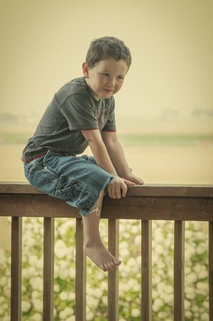 straddle: Cute little boy sitting on the backporch railing while enjoying his summer. Retro  look.
