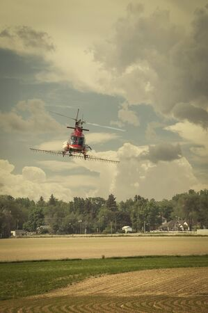 dusting: Helicopter used for crop dusting, spraying fertilizer on a field in nothern Colorado, USA