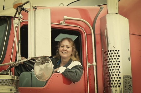 leaning on the truck: Woman truck driver leaning out the drivers side window. Retro instagram look. Stock Photo