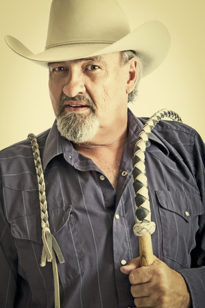 Cowboy holding a bullwhip around his shoulder.  photo