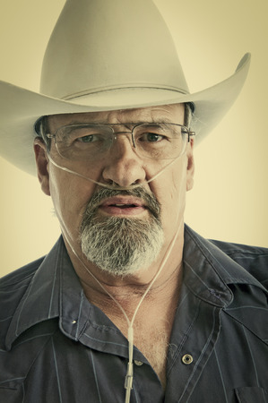 Mature cowboy with a breathing disability, wearing an Oxygen cannula and eyeglasses.  photo