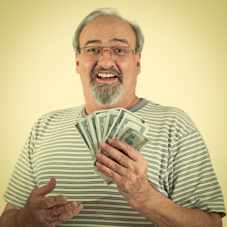 Mature man smiles while holding a handful of American hundred dollar bills. photo