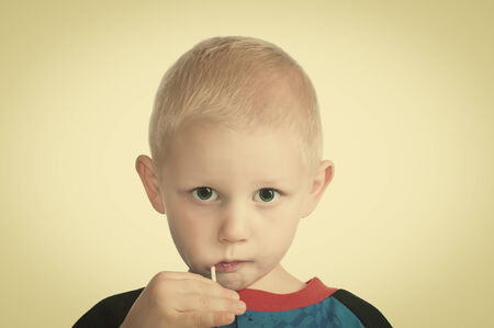 sucker: Cute little blonde boy with a sucker in his mouth.  Stock Photo