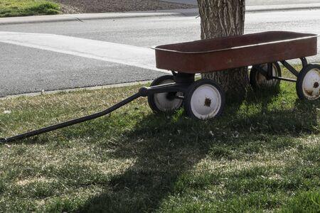 pull toy: Viejo oxidado vagón rojo estacionado debajo de un árbol como decoración de la yarda después de que los niños han crecido y evolucionado.
