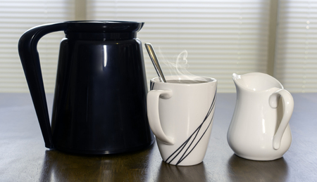 creamer: Fresh mixed cup of coffee next to a carafe and creamer on the kitchen table.