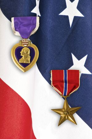 purple heart: US Army Bronze Star and Purple Heart medals over a closeup on an American flag. Editorial