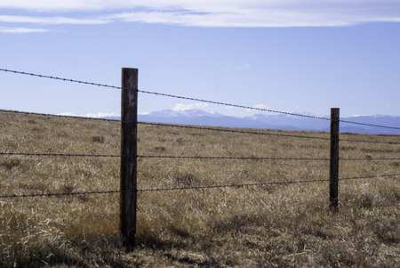 Barbed wire fence to contain livestock on the high plains of Wyoming, USA with the Rocky Mountains in the background.