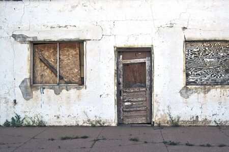 Run-down building abandoned and forgotten with boarded up door and windows Stok Fotoğraf
