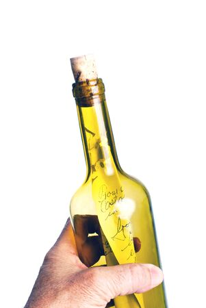 Hand holding a bottle with a note ready to throw or just retrieved. Stock Photo