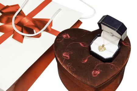 Valentines day gift for a sweetheart. A gold pendant sitting over another unopened heart shaped box
