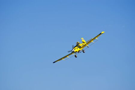 Crop-dusting in eastern Colorado against a pure blue sky. Stock Photo
