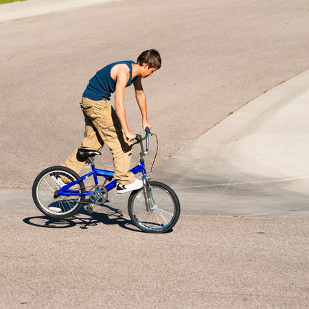 A teenage boy does wheel hops andpeg stands along with other tricks on a BMX bike.